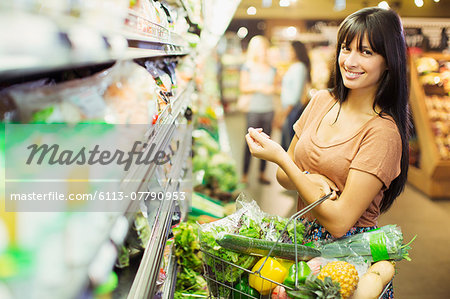 Woman carrying full shopping basket in grocery store Stock Photo - Premium Royalty-Free, Image code: 6113-07790953