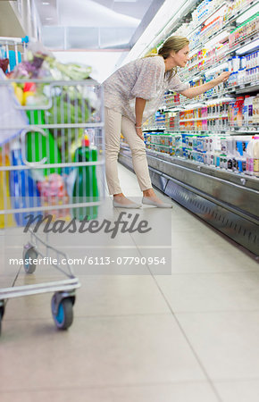 Woman examining products in grocery store Stock Photo - Premium Royalty-Free, Image code: 6113-07790954