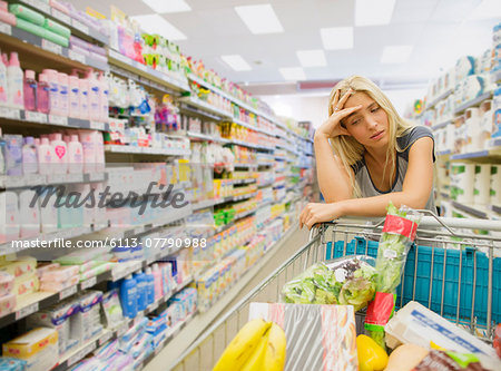 Frustrated woman pushing shopping cart in grocery store Stock Photo - Premium Royalty-Free, Image code: 6113-07790988