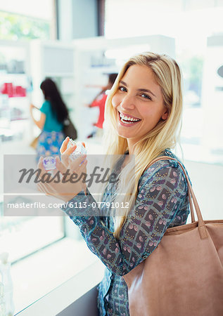 Woman trying on perfume in drugstore Stock Photo - Premium Royalty-Free, Image code: 6113-07791012