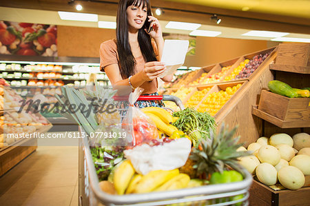 Woman talking on cell phone in grocery store Stock Photo - Premium Royalty-Free, Image code: 6113-07791019