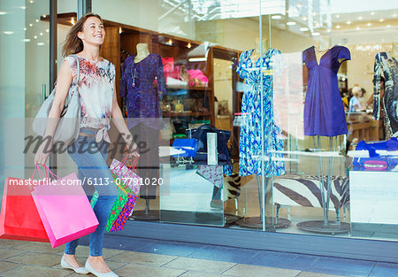 Woman carrying shopping bags in shopping mall Stock Photo - Premium Royalty-Free, Image code: 6113-07791020