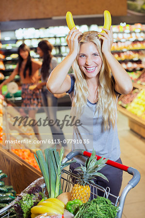 Woman playing with bananas while shopping in grocery store Stock Photo - Premium Royalty-Free, Image code: 6113-07791035