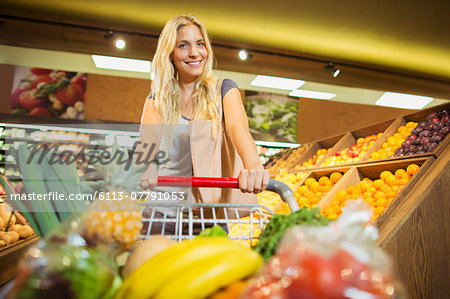 Woman pushing full shopping cart in grocery store Stock Photo - Premium Royalty-Free, Image code: 6113-07791053