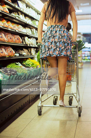 Woman playing on shopping cart in grocery store Stock Photo - Premium Royalty-Free, Image code: 6113-07791070