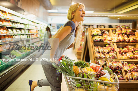 Woman playing with shopping cart in grocery store Stock Photo - Premium Royalty-Free, Image code: 6113-07791080