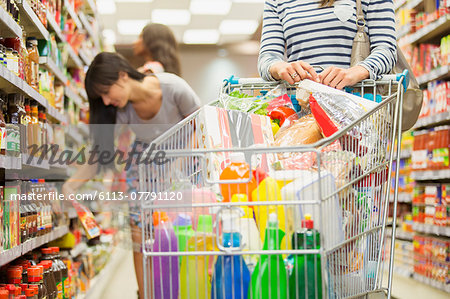 Woman pushing full shopping cart in grocery store Stock Photo - Premium Royalty-Free, Image code: 6113-07791120