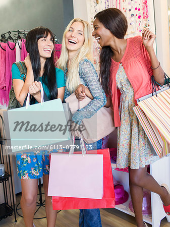 Women carrying shopping bags in clothing store Stock Photo - Premium Royalty-Free, Image code: 6113-07791123