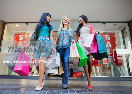 Low angle view of women carrying shopping bags outside clothing store Stock Photo - Premium Royalty-Free, Image code: 6113-07791132