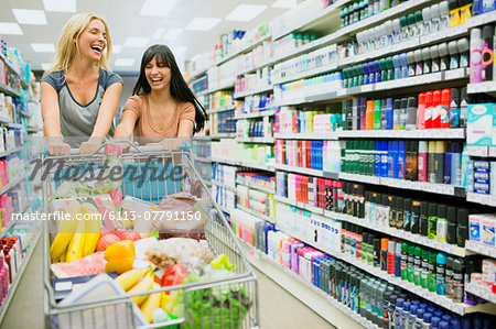 Women pushing full shopping cart together in grocery store Stock Photo - Premium Royalty-Free, Image code: 6113-07791150