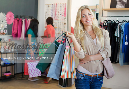 Woman carrying shopping bags in clothing store Stock Photo - Premium Royalty-Free, Image code: 6113-07791152