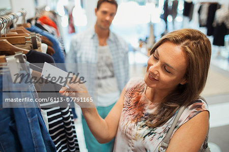 Woman checking tag while shopping in clothing store Stock Photo - Premium Royalty-Free, Image code: 6113-07791165