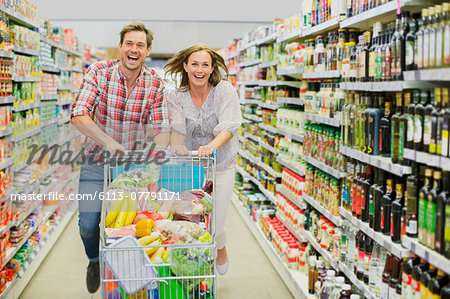 Couple playing with shopping cart in grocery store aisle Stock Photo - Premium Royalty-Free, Image code: 6113-07791171