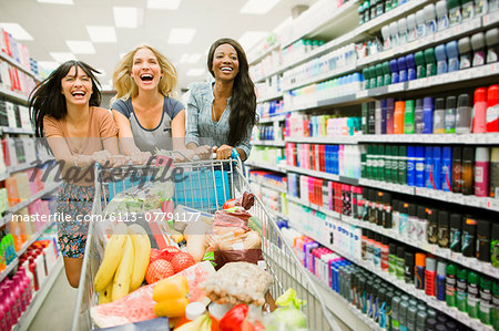 Women playing with shopping cart in grocery store aisle Stock Photo - Premium Royalty-Free, Image code: 6113-07791177