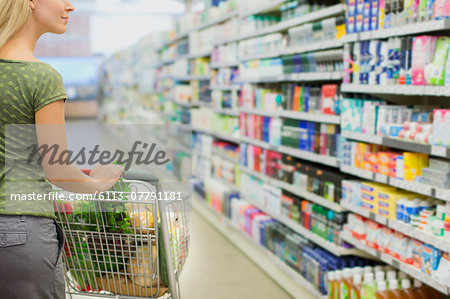 Woman pushing full shopping cart in grocery store Stock Photo - Premium Royalty-Free, Image code: 6113-07791181