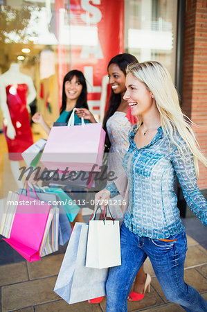 Women carrying shopping bags in shopping mall Stock Photo - Premium Royalty-Free, Image code: 6113-07791216