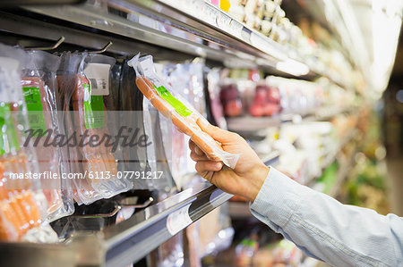 Man selecting product in grocery store Stock Photo - Premium Royalty-Free, Image code: 6113-07791217