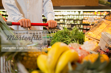 Close up of man pushing full shopping cart in grocery store Stock Photo - Premium Royalty-Free, Image code: 6113-07791227