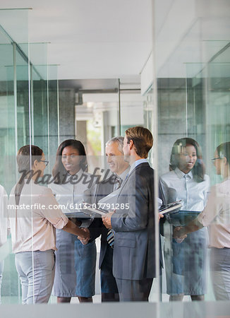 Business people talking in office building Stock Photo - Premium Royalty-Free, Image code: 6113-07791285
