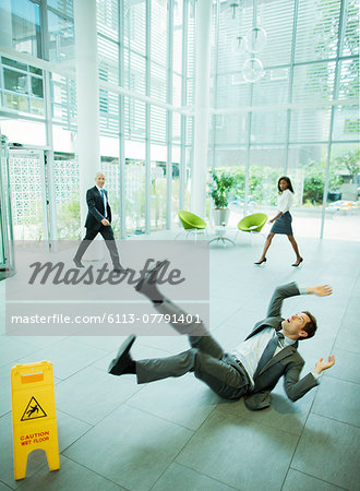 Businessman slipping on floor of office building Stock Photo - Premium Royalty-Free, Image code: 6113-07791401
