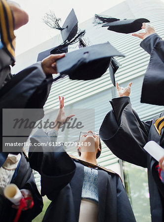Students in gowns throwing caps in the air Stock Photo - Premium Royalty-Free, Image code: 6113-07791489