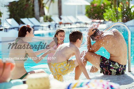 Playful family with two children on poolside Stock Photo - Premium Royalty-Free, Image code: 6113-07808097