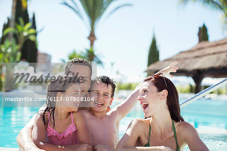 Family with two children enjoying themselves in swimming pool Stock Photo - Premium Royalty-Free, Image code: 6113-07808104