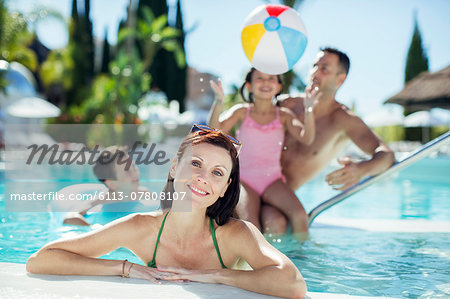 Portrait of smiling woman in swimming pool, family playing with beach ball in background Stock Photo - Premium Royalty-Free, Image code: 6113-07808107
