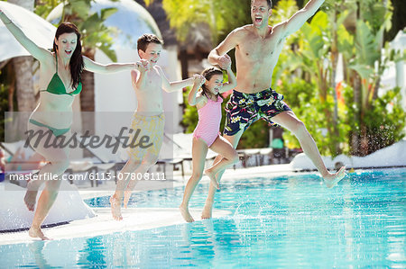 Parents with son and daughter holding hands, jumping into swimming pool Stock Photo - Premium Royalty-Free, Image code: 6113-07808111