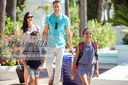 Family with suitcases walking towards tourist resort Stock Photo - Premium Royalty-Free, Image code: 6113-07808118