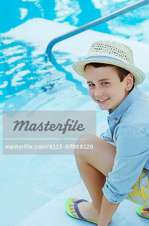 Portrait of smiling boy wearing straw hat crouching by swimming pool Stock Photo - Premium Royalty-Free, Image code: 6113-07808120