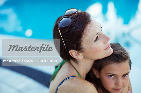 Pensive woman sitting by swimming pool with daughter Stock Photo - Premium Royalty-Free, Image code: 6113-07808126