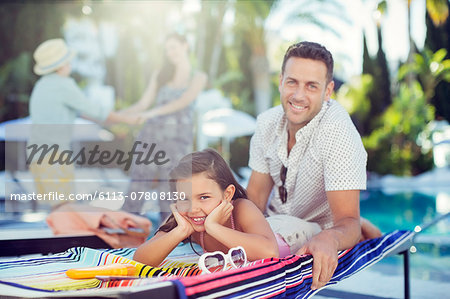 Portrait of smiling father and daughter relaxing by swimming pool, mother and daughter in background Stock Photo - Premium Royalty-Free, Image code: 6113-07808130