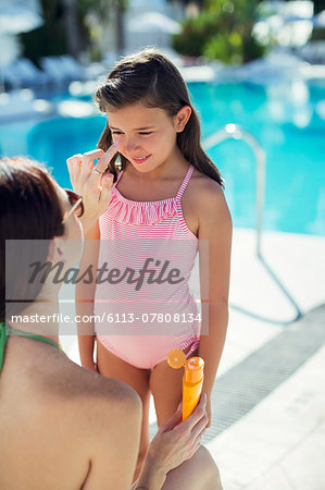 Mother applying suntan lotion on daughter's face by swimming pool Stock Photo - Premium Royalty-Free, Image code: 6113-07808134