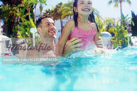 Father with daughter and son playing in swimming pool Stock Photo - Premium Royalty-Free, Image code: 6113-07808139