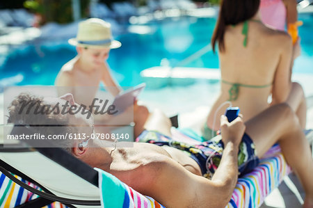 Family with two children sunbathing by resort swimming pool Stock Photo - Premium Royalty-Free, Image code: 6113-07808140
