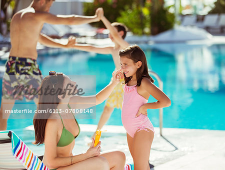 Mother applying suntan lotion on daughter's face by swimming pool Stock Photo - Premium Royalty-Free, Image code: 6113-07808148