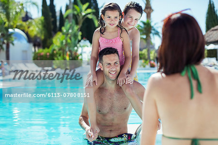 Father giving piggyback ride to his two children in swimming pool Stock Photo - Premium Royalty-Free, Image code: 6113-07808151