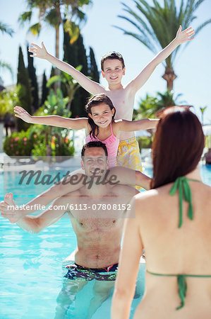 Father giving piggyback ride to his two children in swimming pool Stock Photo - Premium Royalty-Free, Image code: 6113-07808152