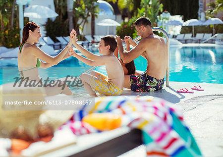 Family with two children enjoying themselves by swimming pool Stock Photo - Premium Royalty-Free, Image code: 6113-07808157