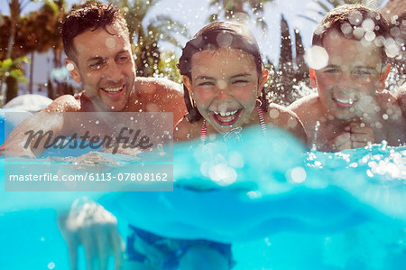 Father swimming with his two children in swimming pool Stock Photo - Premium Royalty-Free, Image code: 6113-07808162