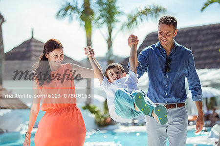 Boy holding hands with his parents by swimming pool Stock Photo - Premium Royalty-Free, Image code: 6113-07808163