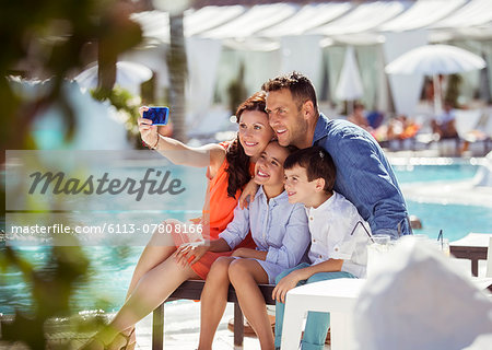 Family with two children taking selfie by resort swimming pool Stock Photo - Premium Royalty-Free, Image code: 6113-07808166