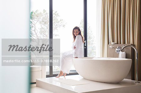 Portrait of smiling woman wearing white bathrobe, sitting on edge of bathtub in bathroom Stock Photo - Premium Royalty-Free, Image code: 6113-07808262