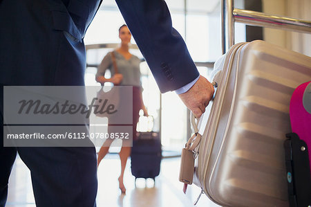 Close up of man wearing suit grabbing silver suitcase, woman in background Stock Photo - Premium Royalty-Free, Image code: 6113-07808532
