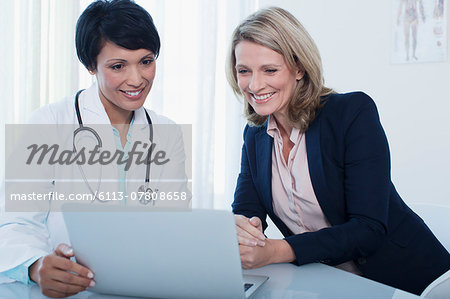 Doctor and patient using laptop in hospital office Stock Photo - Premium Royalty-Free, Image code: 6113-07808658