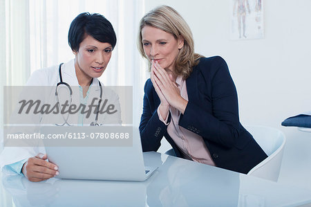 Female doctor and patient using laptop in hospital office Stock Photo - Premium Royalty-Free, Image code: 6113-07808688