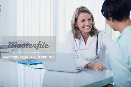 Smiling female doctor and woman sitting at desk in office Stock Photo - Premium Royalty-Free, Image code: 6113-07808703