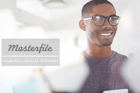 Portrait of young smiling businessman wearing glasses in office Stock Photo - Premium Royalty-Free, Image code: 6113-07808883