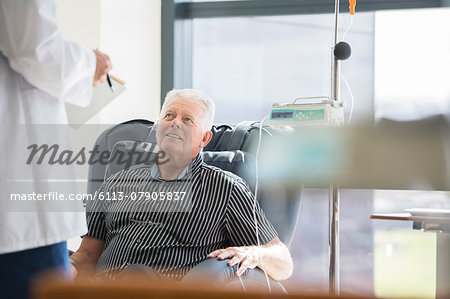 Doctor talking to patient receiving medical treatment in hospital ward Stock Photo - Premium Royalty-Free, Image code: 6113-07905837